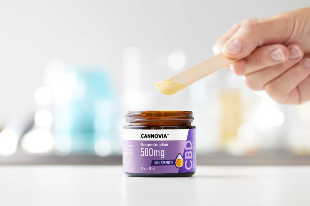 Cannovia CBD therapeutic gel with hand using a wooden stick - Cannabis CBD Photography