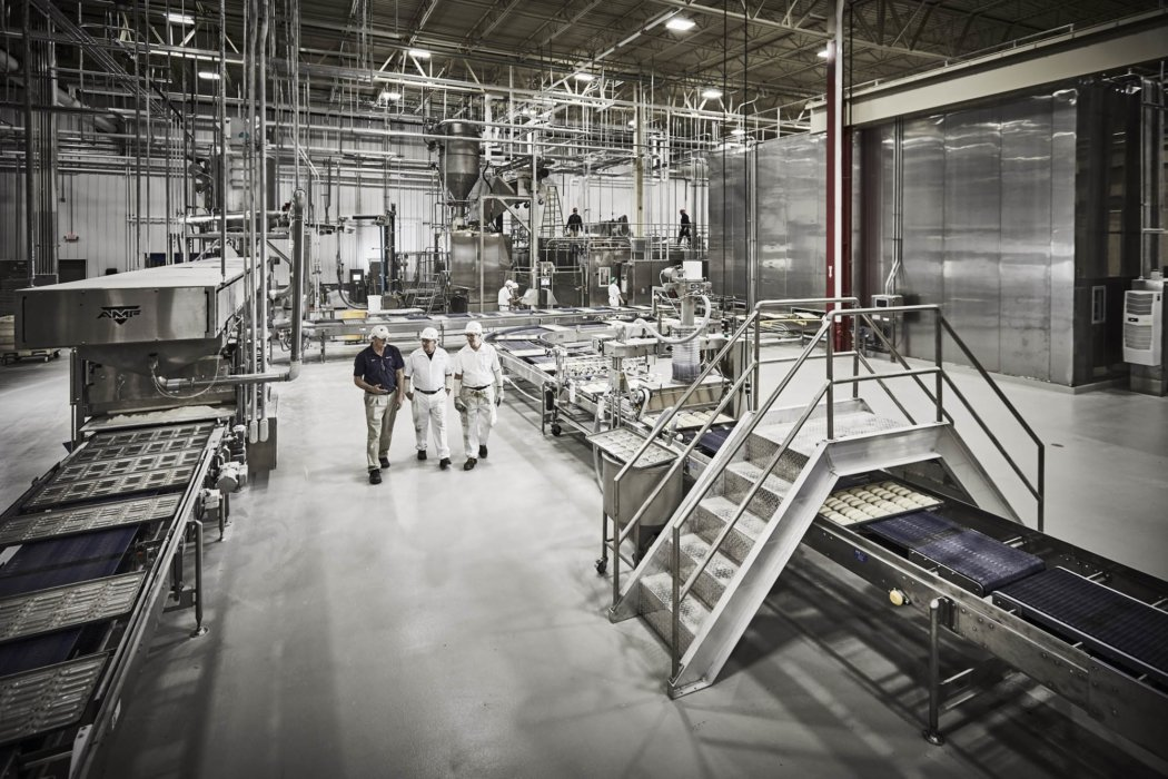 Three workers walking through a clean industrial baking facility