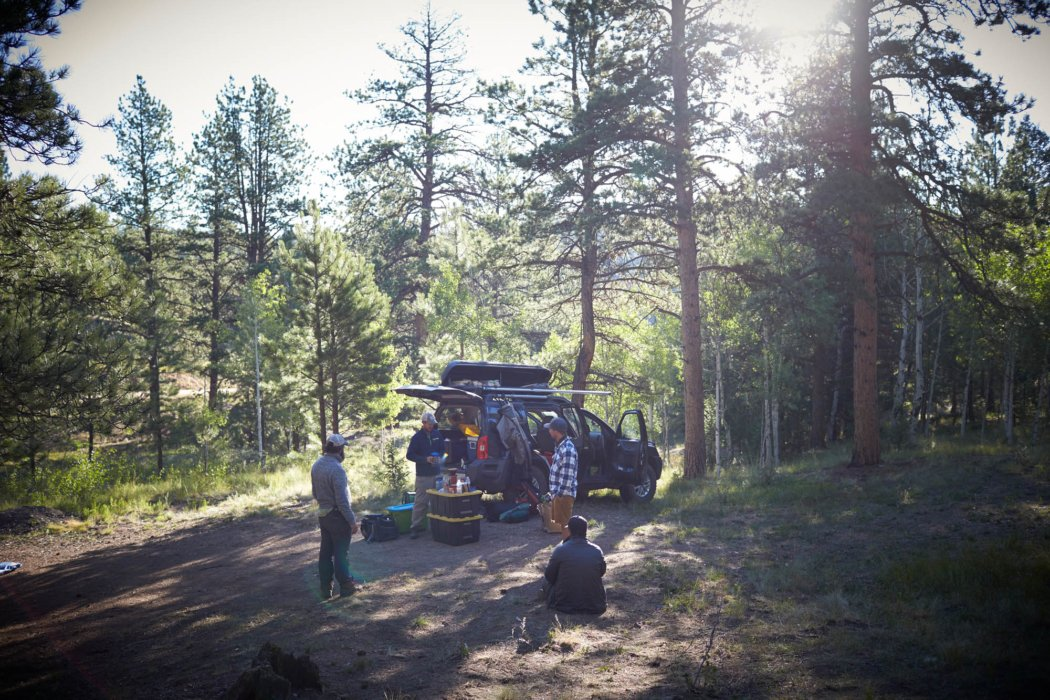 Four fisherman at a campsite enjoying the afternoon in a clearing