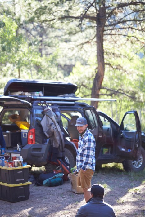 Two fisherman enjoying a moment at a campsite by their SUV car