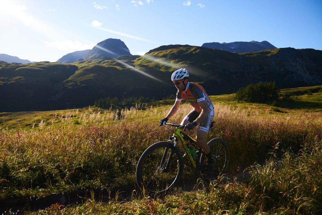A cyclist riding through a beautiful field in a mountain range - bike photo