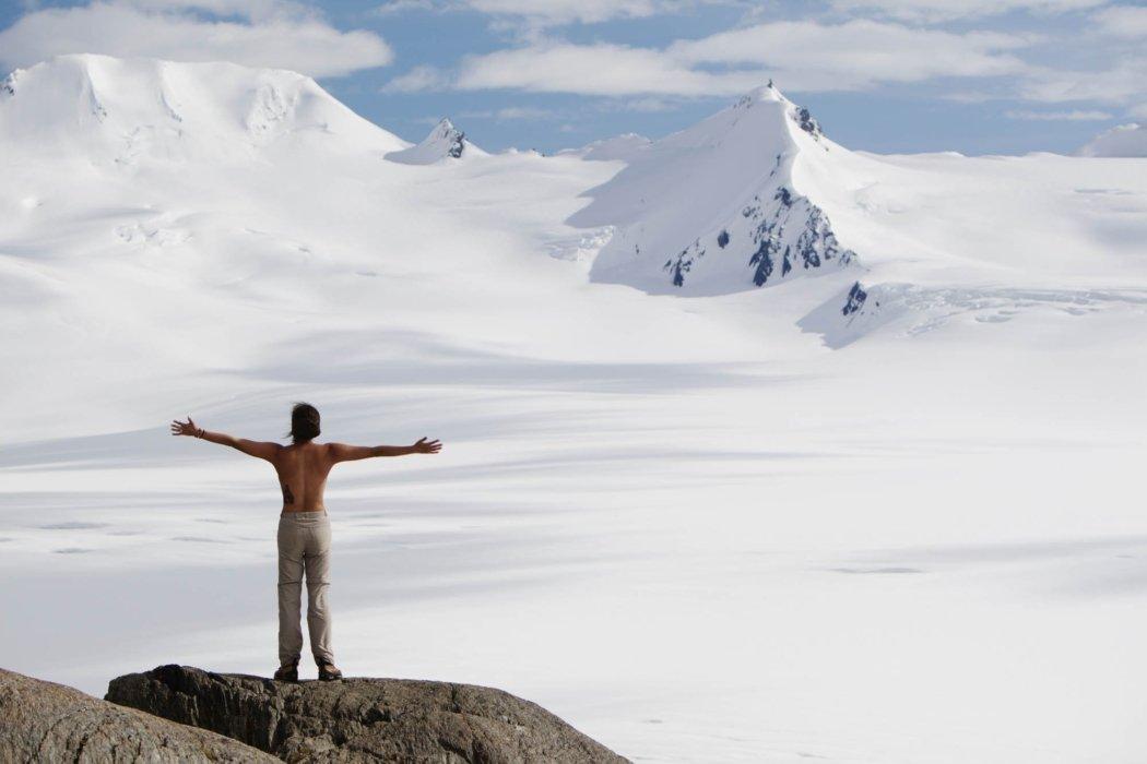 A woman on a ridge of a wide open snowy mountain