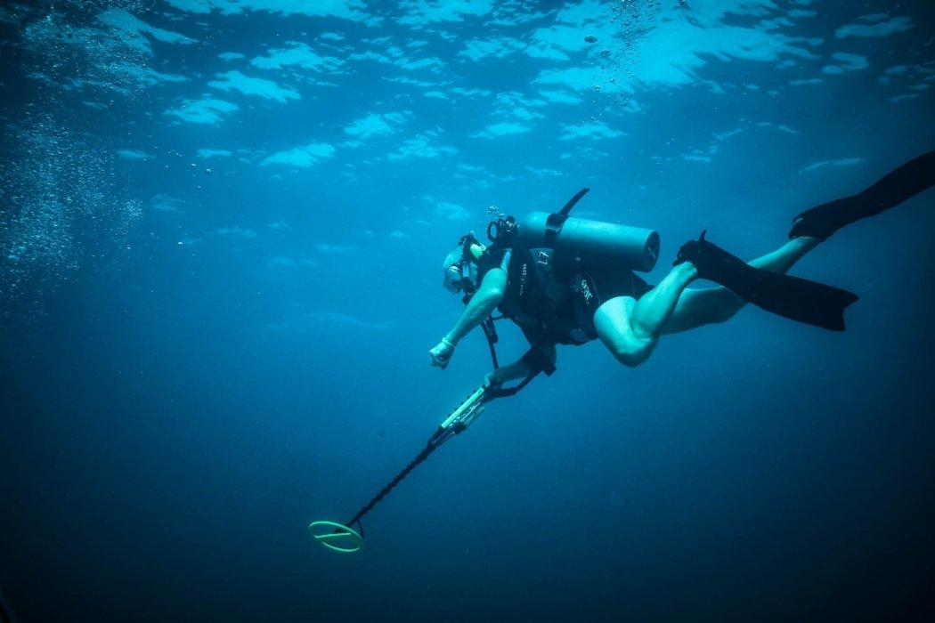 A diver with a metal detector in a dark blue ocean