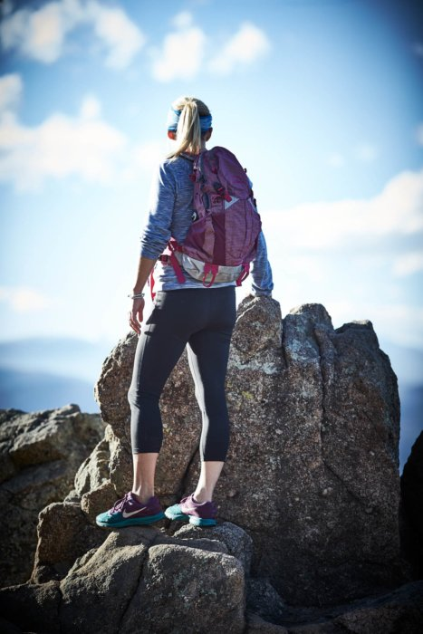 A woman hiker on a rocky mountain tail looking over the landscape with a backpack