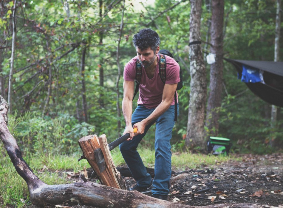 A man at a campsite splitting wood with an axe