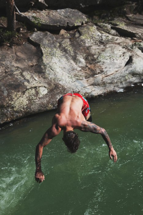 A man doing a flip in the river - hiking - camping