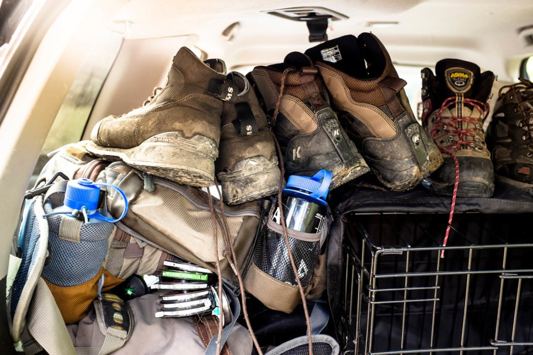 Numerous hiking boots covered in mud in the back of an SUV