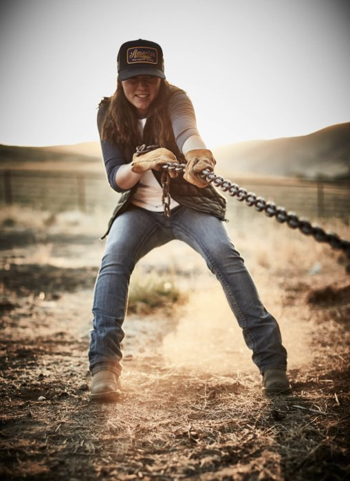 A woman rancher holding on to heavy chains and working hard