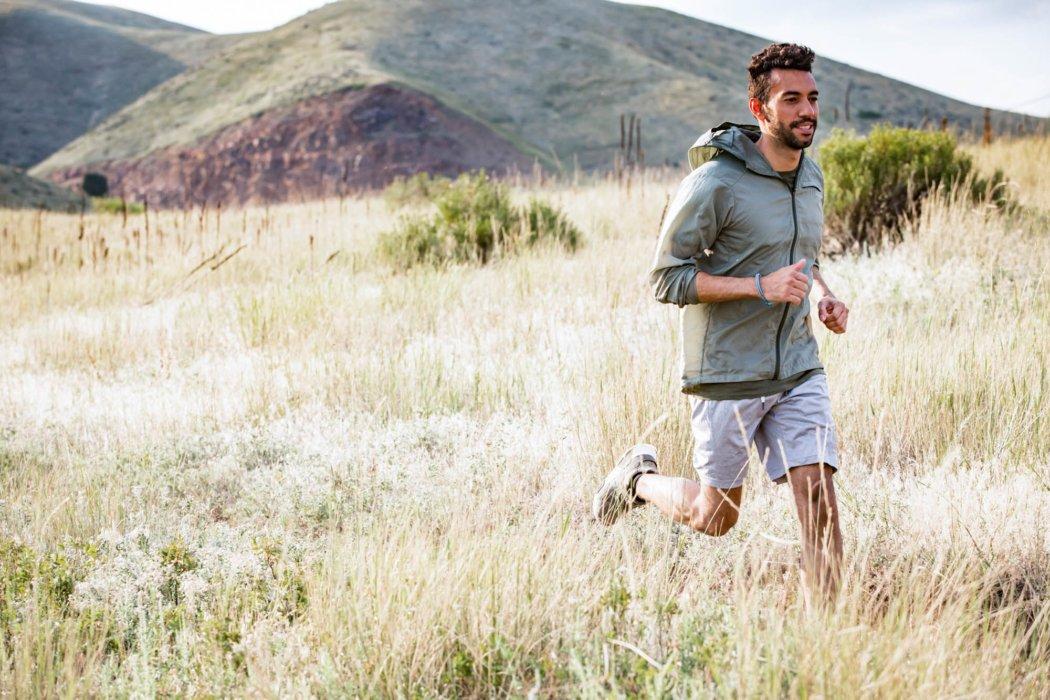 A hiker running through a tall grass mountain field