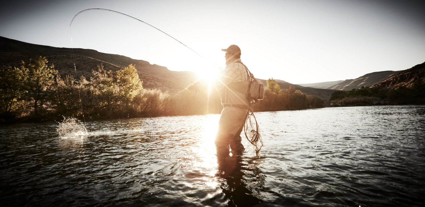 A fisherman with a a fly rod with a fish on a the line in a sunny western river