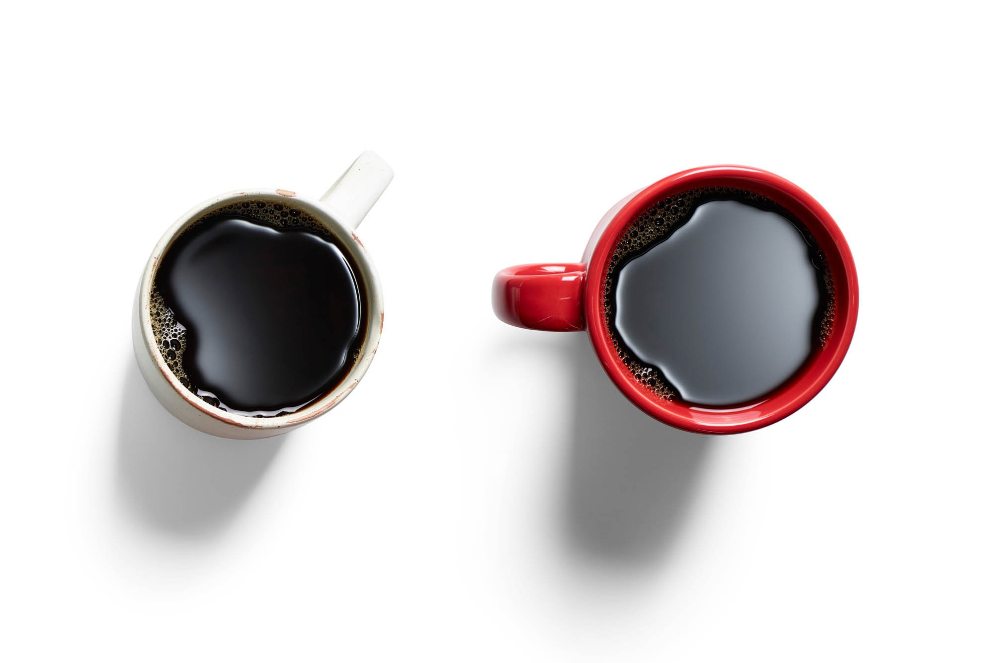 Two cups of black coffee overhead. Red cup and white cup
