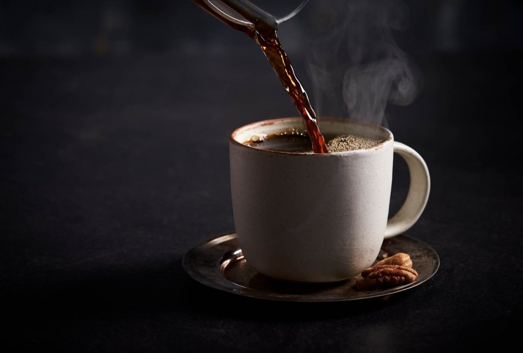 A coffee cup fast motion photo with black coffee with nuts pouring