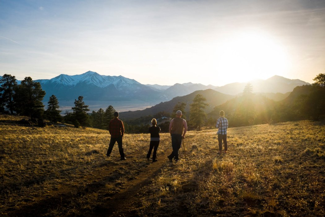 Four friends standing in field at sun set - after a hike