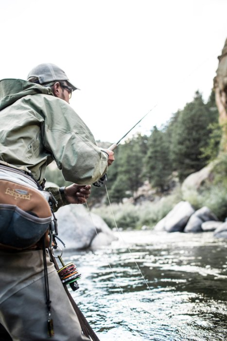 Fly fisherman leaning into casting