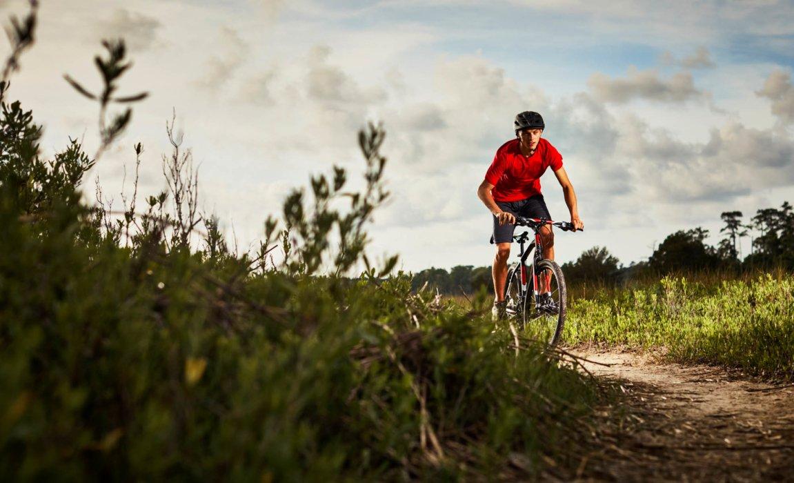 A cyclist riding a royce uninon bike in a rugged terrain