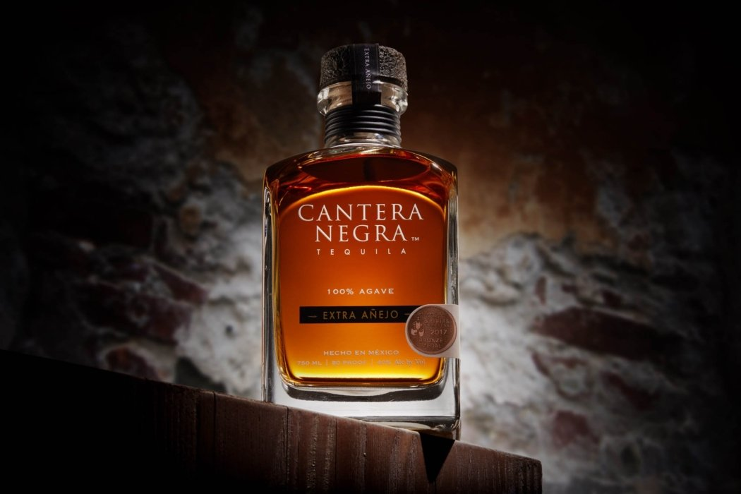 A glowing and glorious shot of tequila extra anejo in front of a brink wall