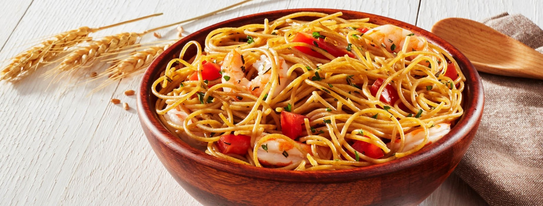 wooden bowl holding fresh food wheat noodles with tomatoes and shrimps