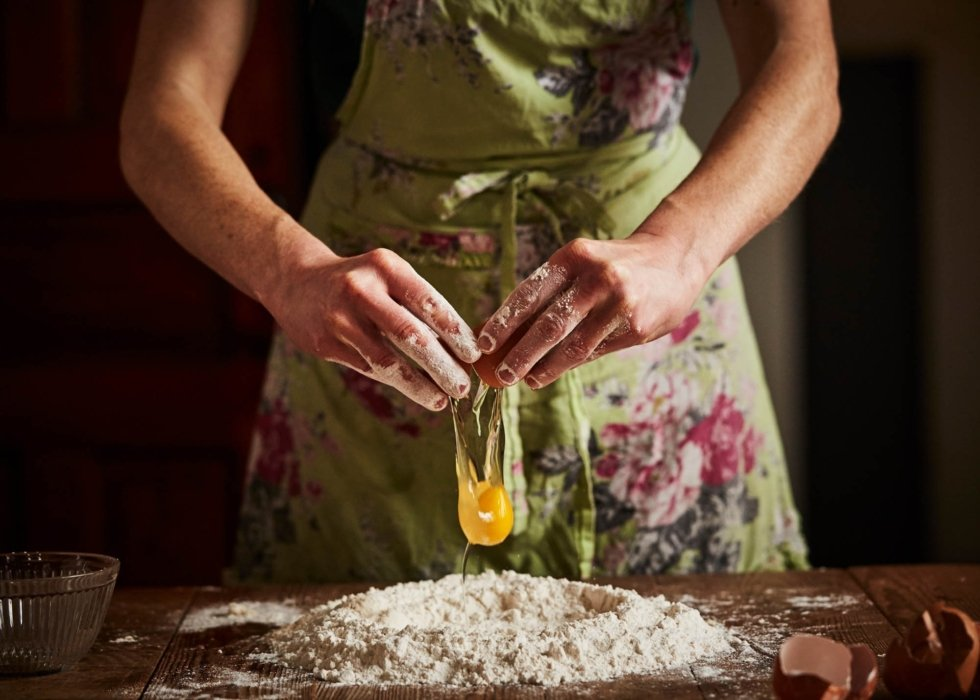 woman breaking a fresh food egg on flour on a wooden table