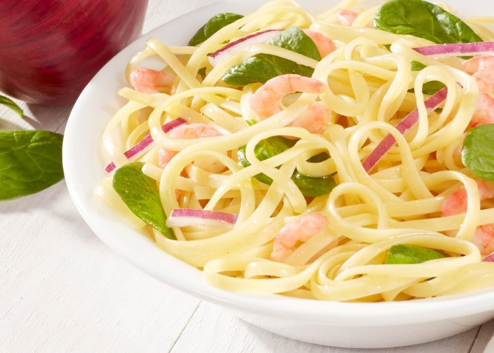 white bowl of long food noodle and cooked pink skimps and spinach