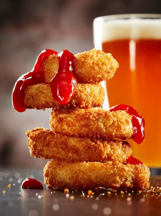 pile of fresh chicken nuggets with dripping ketchup with beer behind