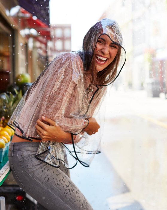 woman wearing clear raincoat smiling getting rained on