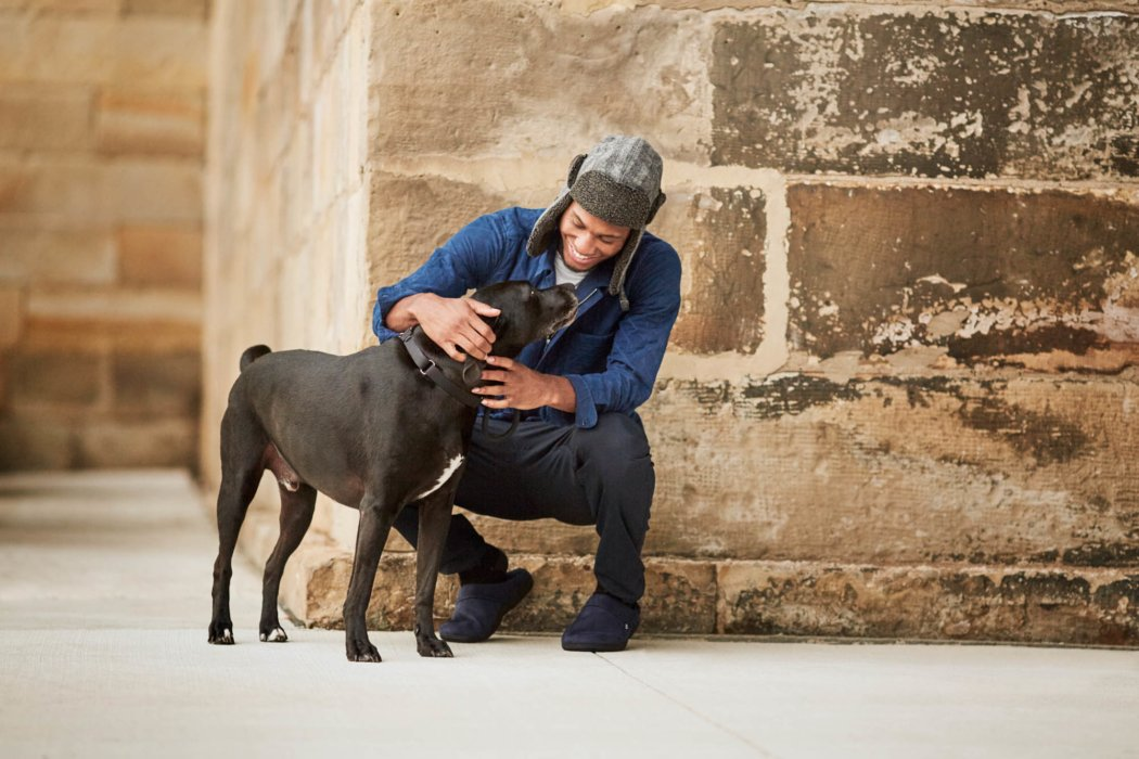 brown wall background outside young man kneeling down petting to a black and white dog