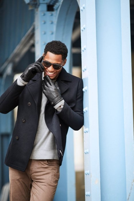 Outside young man smiling with a black sunglasses talking on his phone