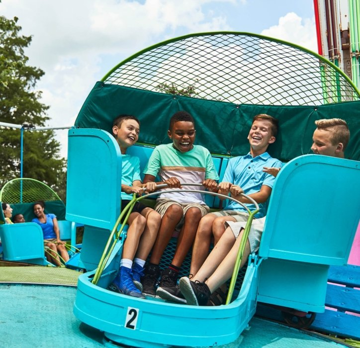 groups of young boys sitting all together and having a good time on a ride at a amusement park