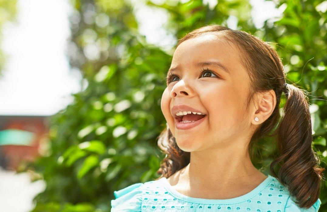 outside brown hair little girl in blue dress smiling
