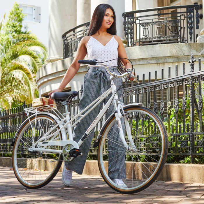Woman with striped pant next to a white bike outside