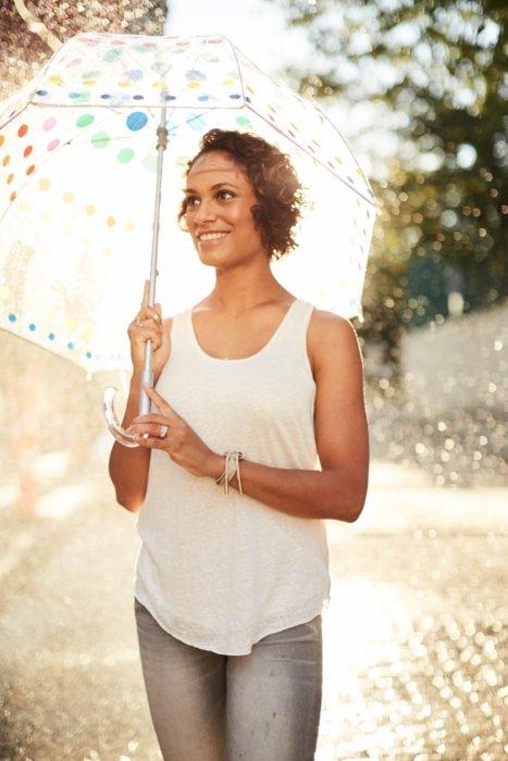curly short hair woman holding a clear rainbow umbrella in a sunny raining day