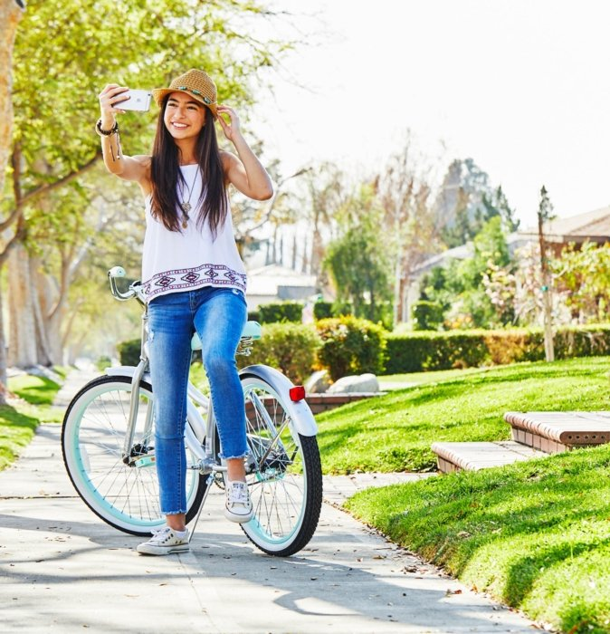 young woman with a brown hat sitting on her blue bike taking a picture of herself on cellphone