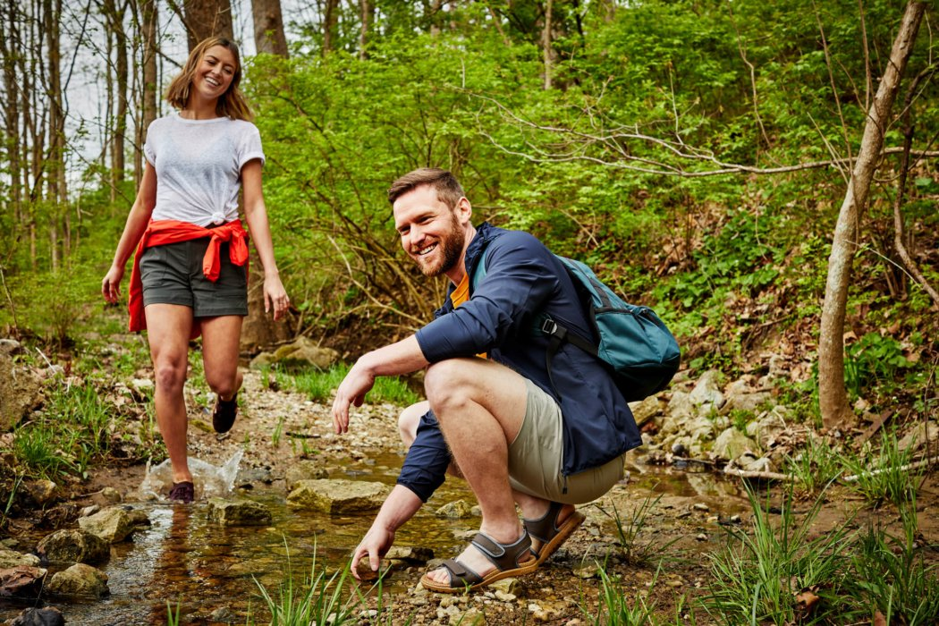 A woman walking in stream with a man with rocks