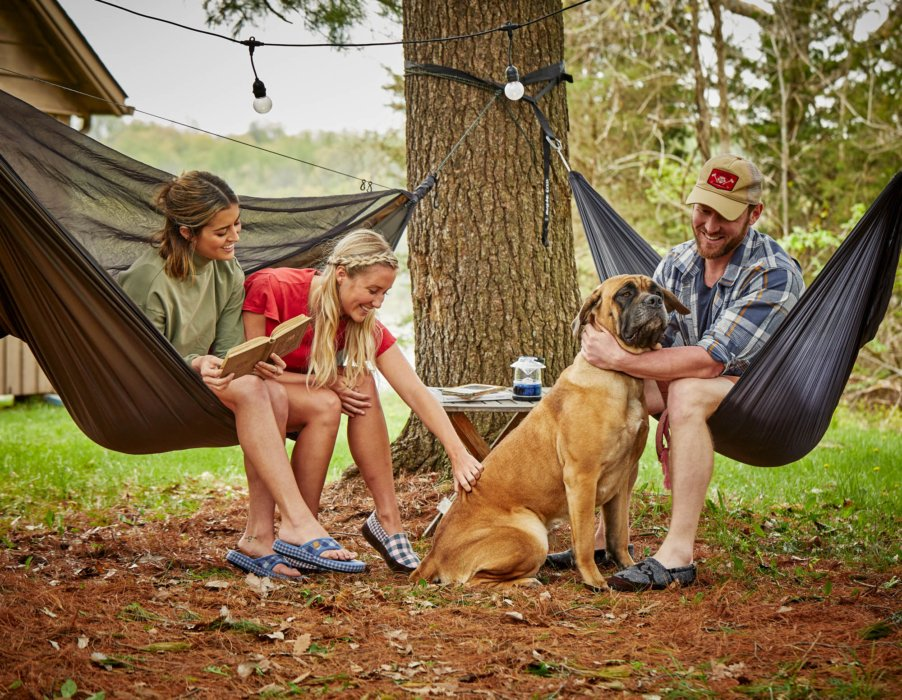 Two women, a man, a dog, in hammocks - lifestyle photograph wearing Acorn Shoes