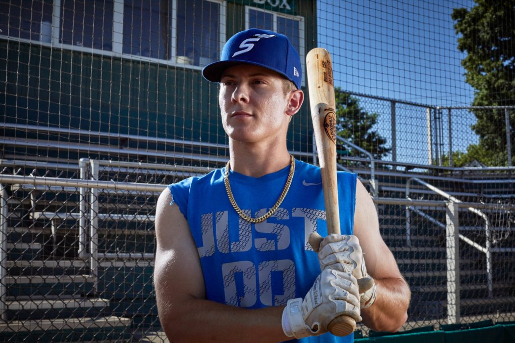 Portrait of a young base ball player with a bat and chain around neck