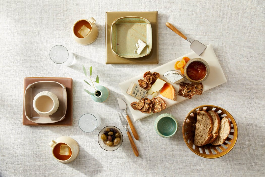 A selection of hand made craft stoneware with charcuterie spread and food