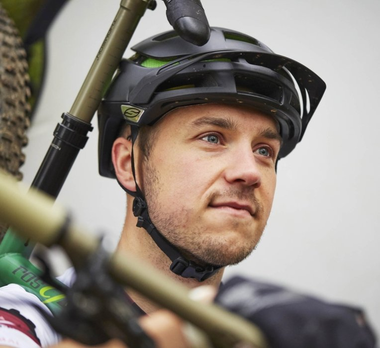Portrait of a cyclist wearing a helmet while carrying his bike