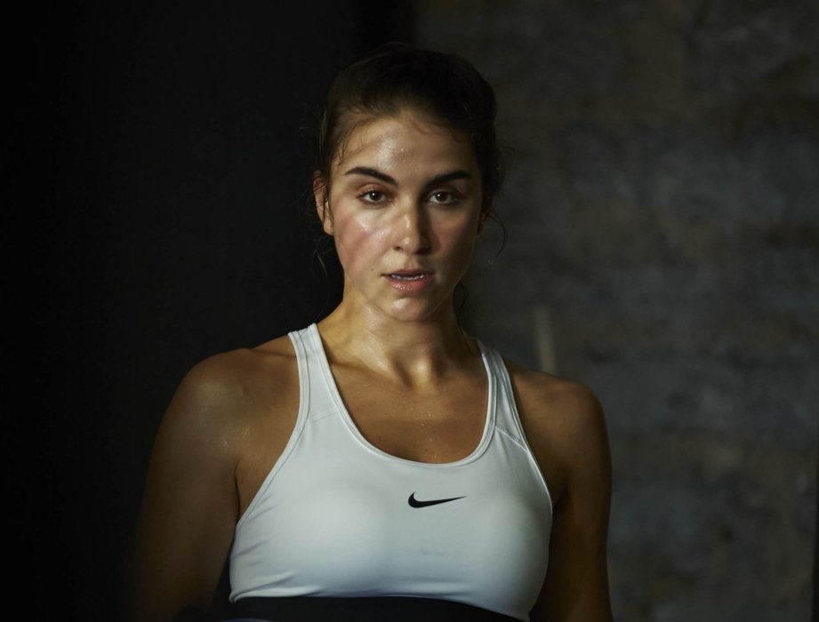 A female boxer breathing heavy during training for the sport