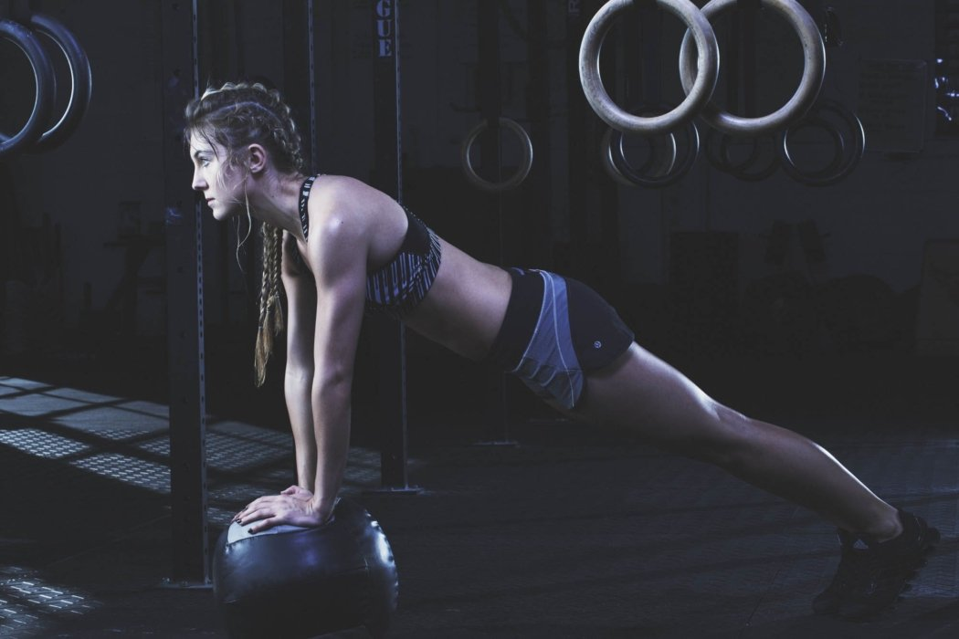 A young female sports athlete training at gym doing pushups