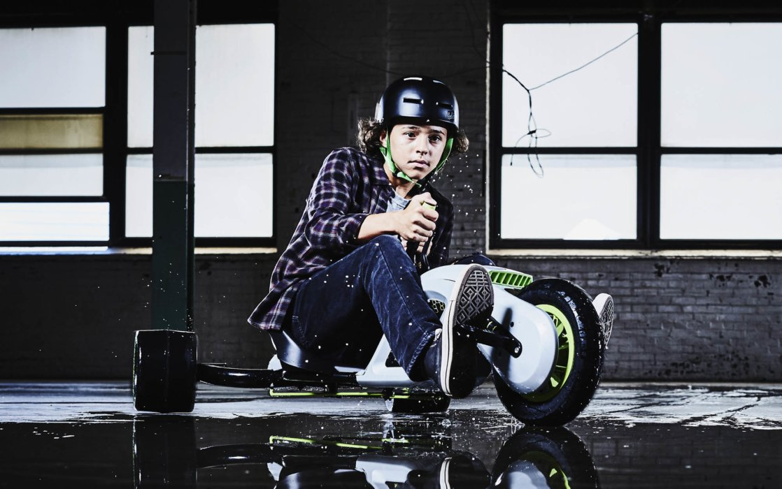 A kid on a motorized tricycle in a warehouse