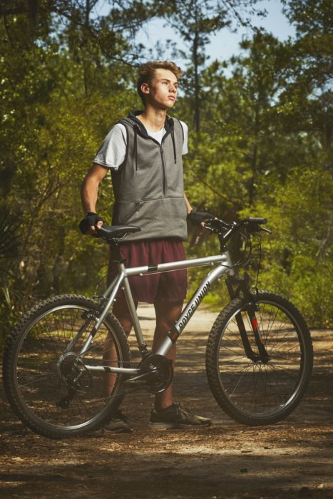 A male bike rider standing next to his bike in the woods