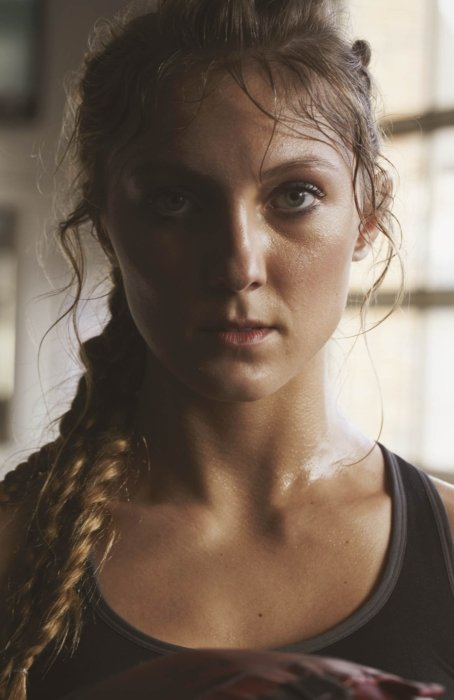 A portrait of a female athlete looking sweaty after working out