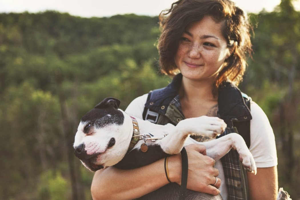 A woman carrying her dog while hiking