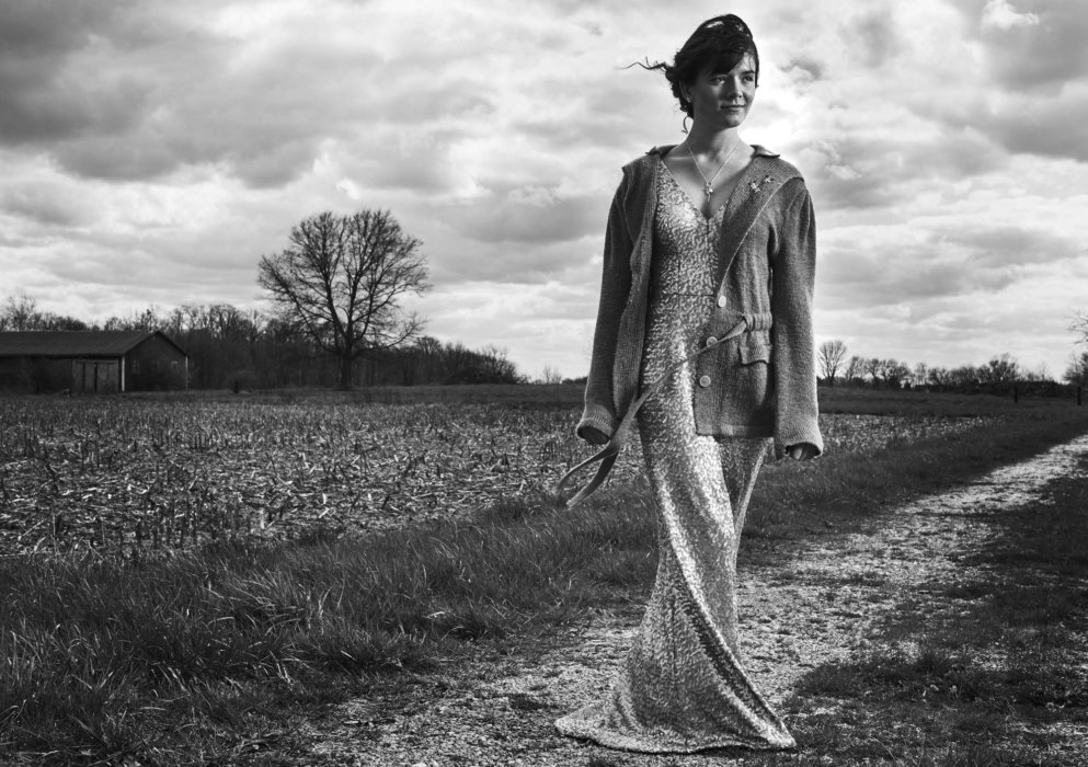 A woman wearing unique a dresse and sweater in a desolate farm setting