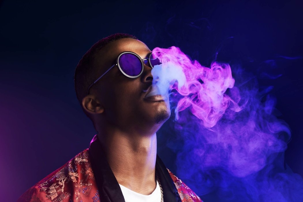 A young man blowing smoke in for an urban lifestyle look