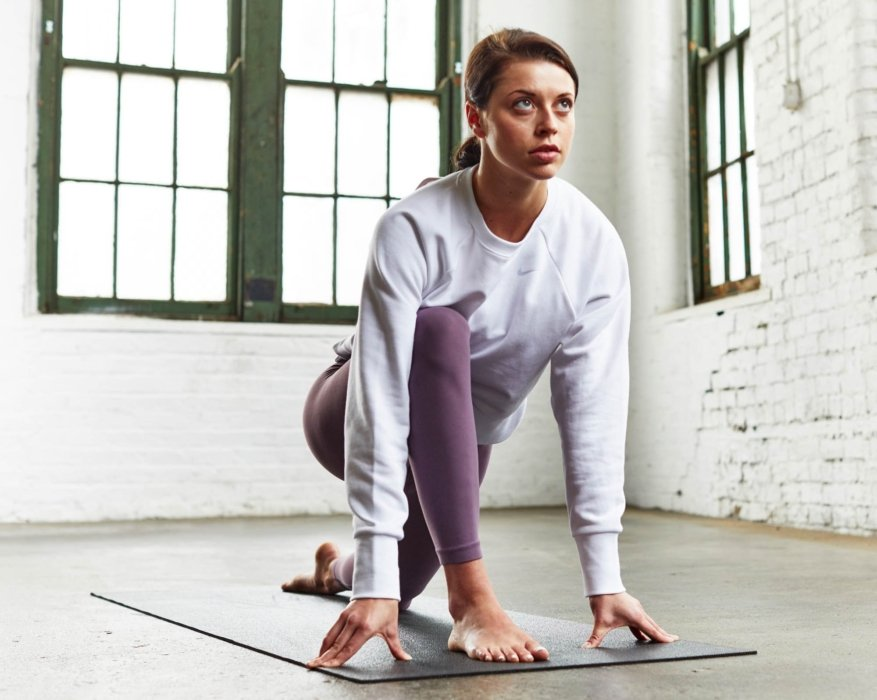 A young woman doing yoga and stretching wearing a sweatshirt and yoga apparel