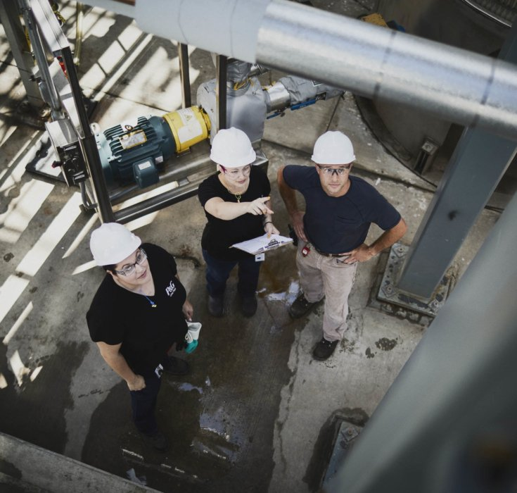 Three workers inspecting an outdoor industrial installation