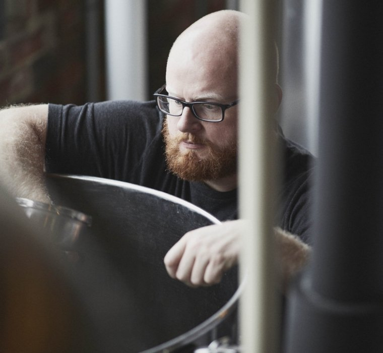 A worker at a brewery inspecting barrels