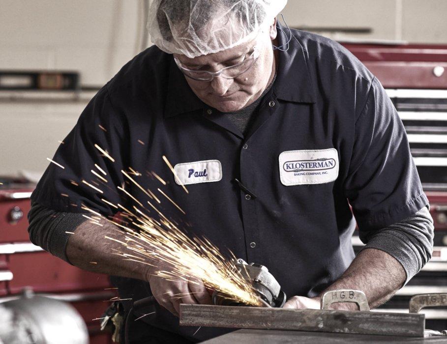A male repairman grinding metal in a industrial workplace