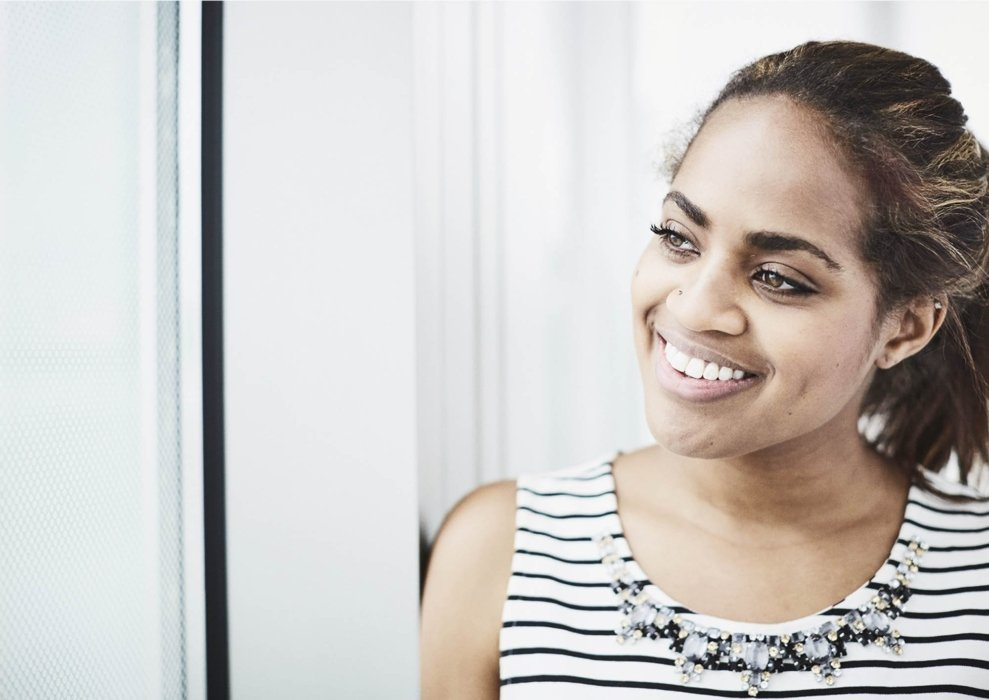 A young woman smiling in a corporate workplace